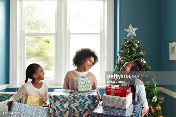 Happy sisters carrying Christmas gifts at home