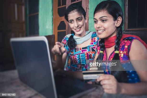 Happy sisters doing online shopping at home.