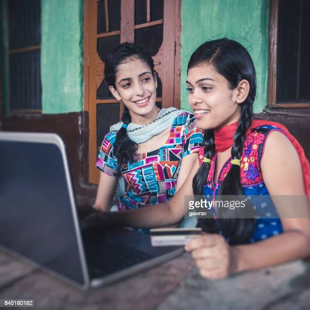 happy sisters doing online shopping at home. - salwar kameez stock pictures, royalty-free photos & images