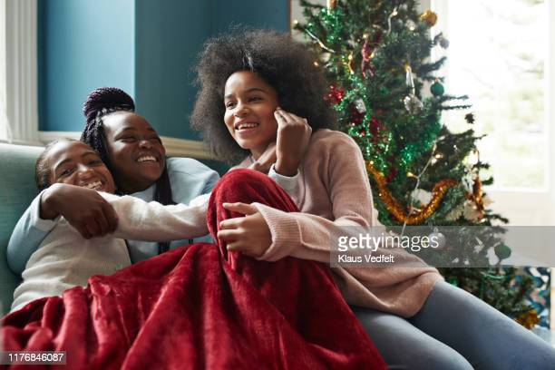 Happy sisters embracing while sitting on sofa