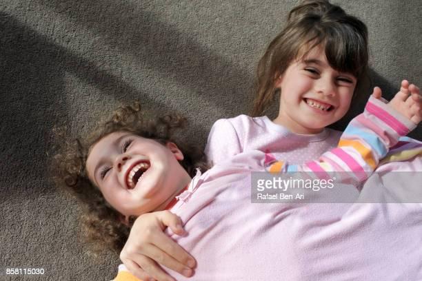 happy sisters having fun at home - rafael ben ari ストックフォトと画像