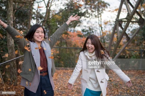 Glücklich Schwestern spielen mit abgefallenen Blättern