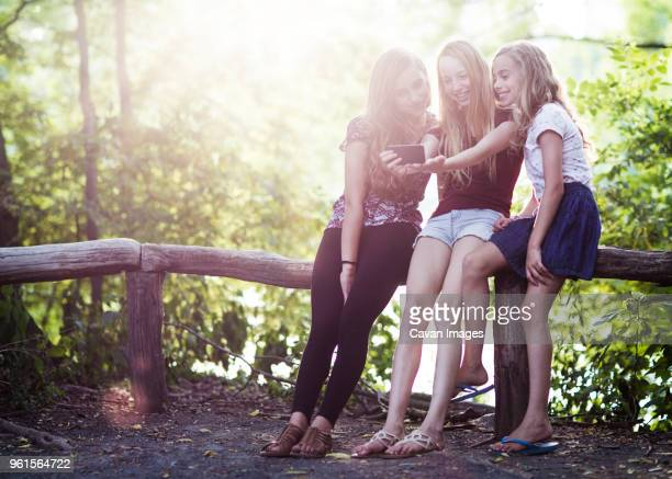 happy sisters taking selfie while resting on railing at park - girls with short skirts - fotografias e filmes do acervo