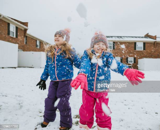 happy sisters throw snow and have snowball fight on winter day - 2 5 months stock pictures, royalty-free photos & images