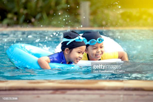 happy sisters with inflatable rings swimming in pool - asian twins stock photos and pictures