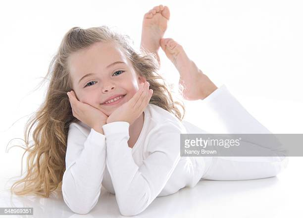 happy six year old girl on white - barefoot feet up lying down girl stock photos and pictures