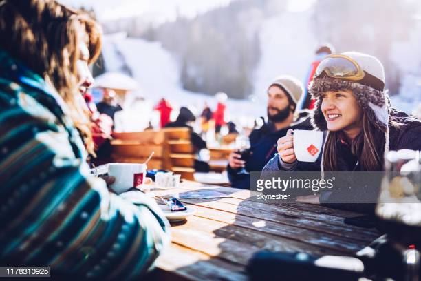 happy skiers talking on a break in a cafe at mountain. - skiing stock pictures, royalty-free photos & images