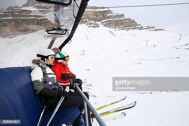 Femmes et les hommes heureux les skieurs sur les remontées mécaniques