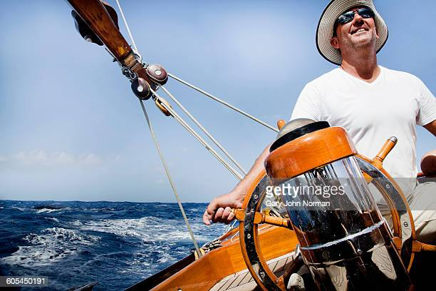 Happy skipper at helm of classic yacht