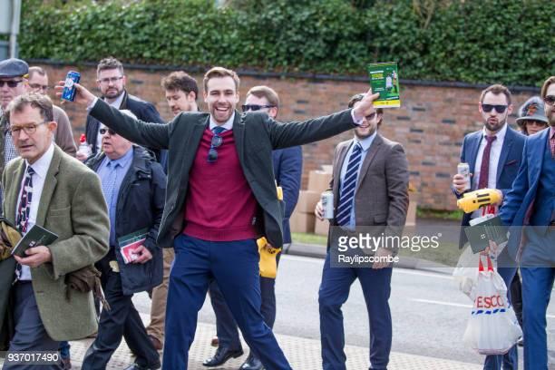 happy, slightly drunk racegoer walking through cheltenham, towards the world famous cheltenham national hunt festival horse races - national drunk stock photos and pictures