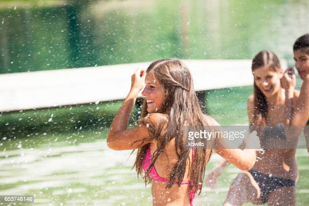 happy Slovenian teenage girls splash and play in picturesque Lake Bled Slovenia