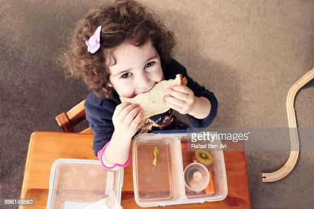 happy small girl eats sandwich - rafael ben ari stock pictures, royalty-free photos & images