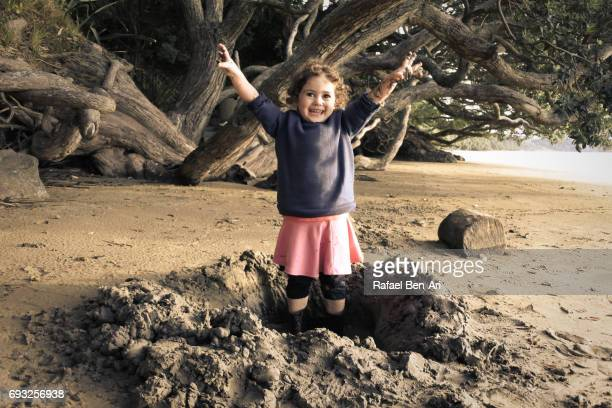 happy small girl plays on the beach - grittywomantrend stock photos and pictures