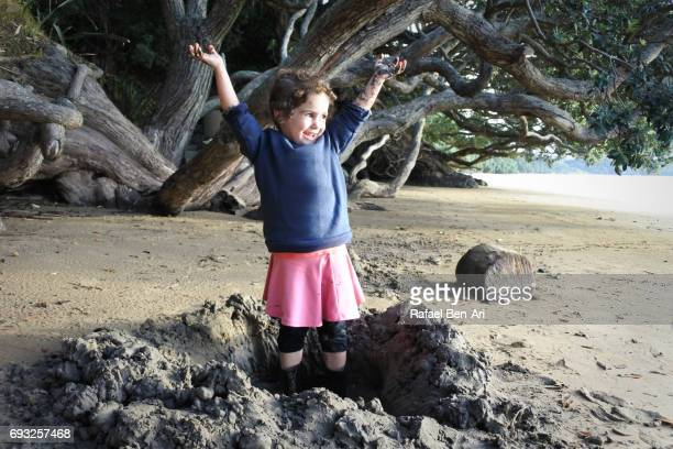 Happy small girl plays on the beach