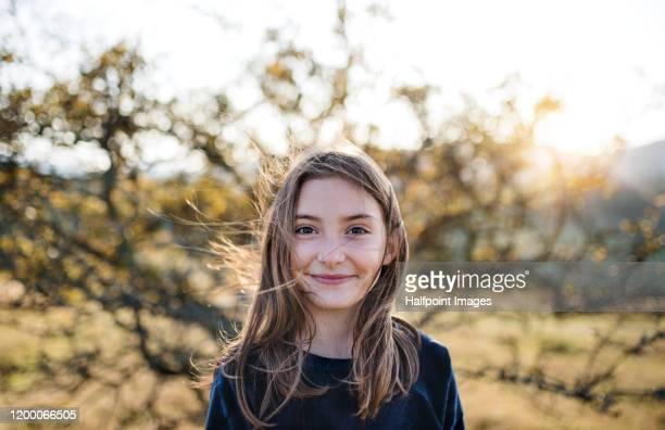 a happy small girl standing outdoors in nature in autumn. - one girl only stock pictures, royalty-free photos & images