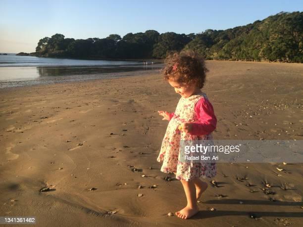 happy small girl  walking on empty beach - rafael ben ari stock-fotos und bilder