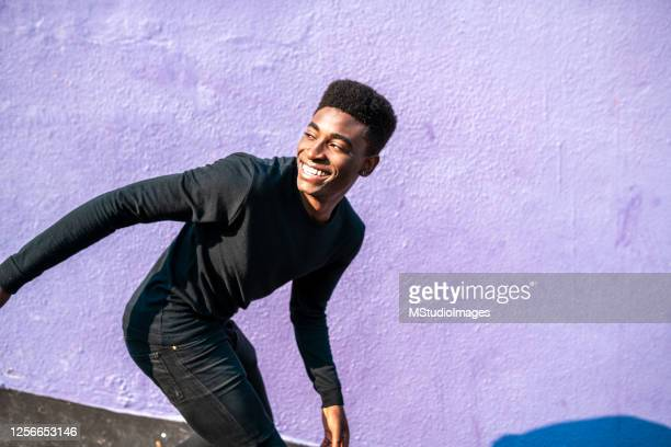 happy smiling african young man. - lilac fashin stock pictures, royalty-free photos & images