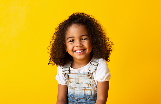Happy smiling african-american child girl, yellow background 1168369629