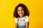 Happy smiling african-american child girl, yellow background