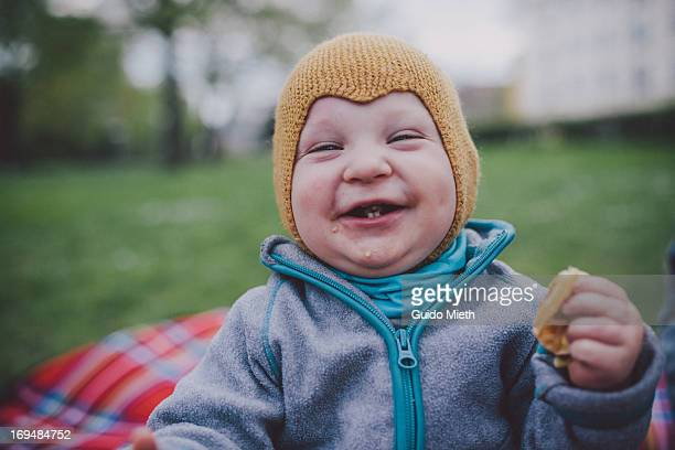 Happy smiling baby boy eating cake outdoor.
