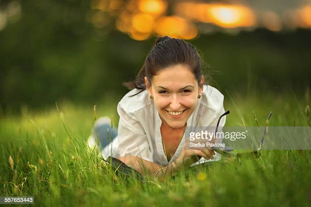 Happy smiling beautiful woman lying in grass