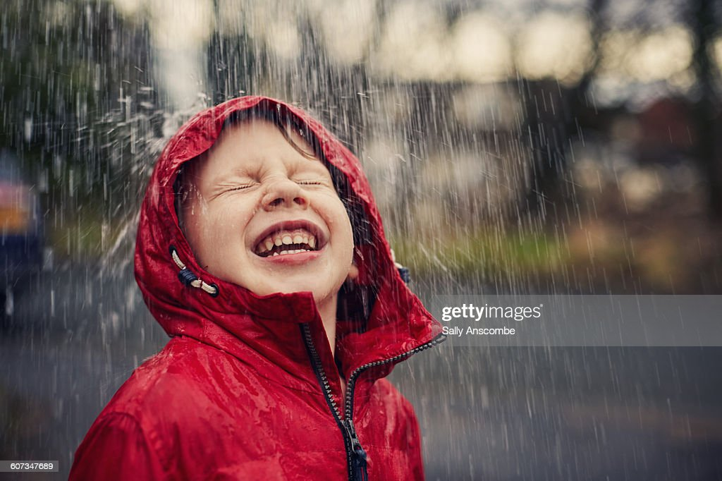 Happy smiling boy in the rain : Stock Photo