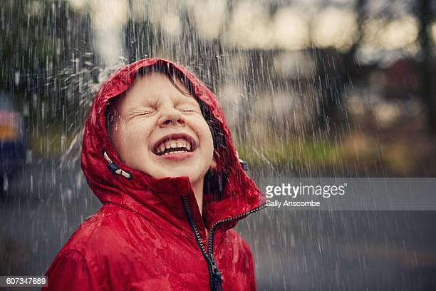 happy smiling boy in the rain - wetter stock-fotos und bilder