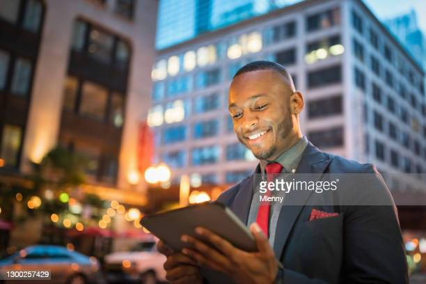 happy smiling chicago businessman using modern 5g tablet computer - mlenny stock pictures, royalty-free photos & images