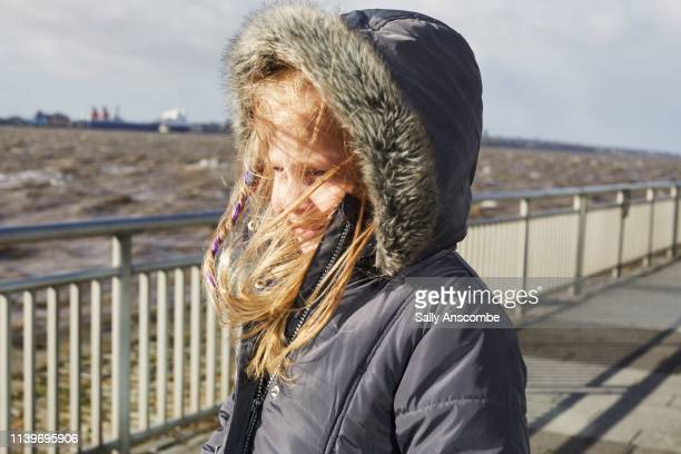 happy smiling child outdoors with hair blowing in the wind - sally anscombe stock pictures, royalty-free photos & images