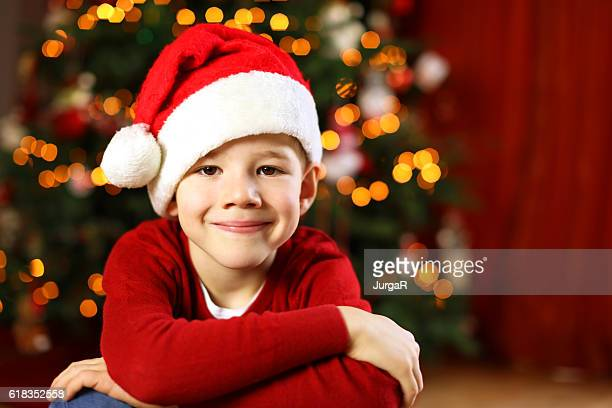 Happy Smiling Child with a Red Santa Hat at Christmas