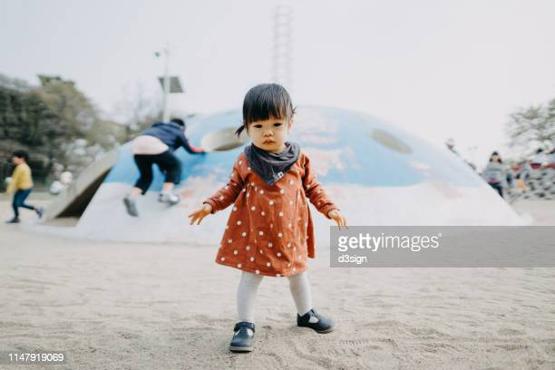 a happy, smiling cute asian toddler girl having fun in outdoor sand playground - baby girls stock pictures, royalty-free photos & images