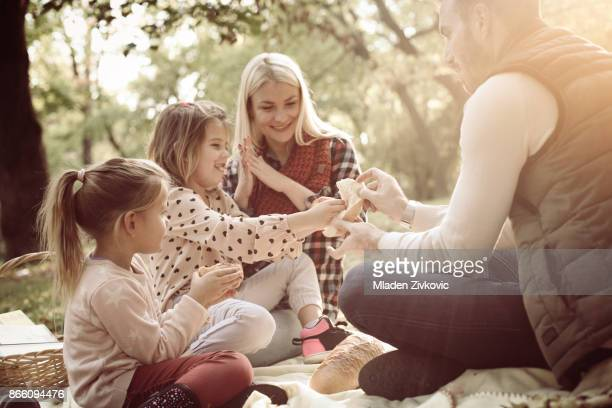 Happy smiling family having picnic together in park and talking.