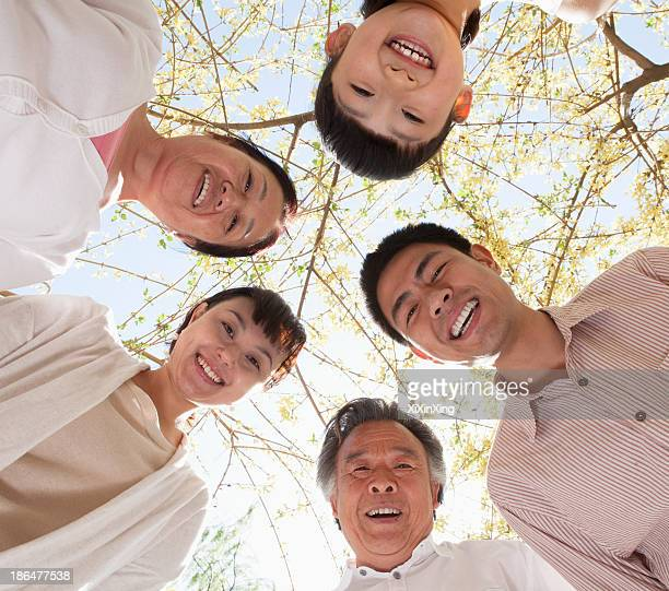 Happy smiling family in a circle looking down in a park in the springtime