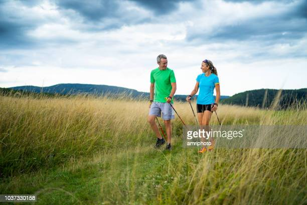 happy smiling fitness instructor and client nordic walking together in rural landscape