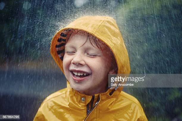 Happy smiling little boy in the rain