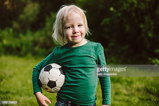 Happy smiling little girl holding a football
