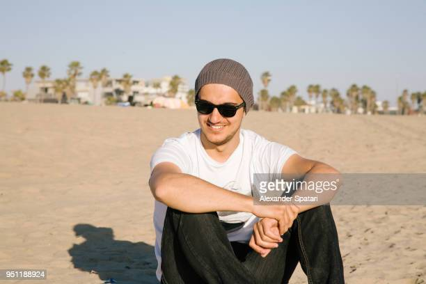 happy smiling man in sunglasses sitting on the beach and smiling - サンタモニカ ストックフォトと画像