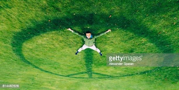 Happy smiling man laying on the peace symbol on the grass