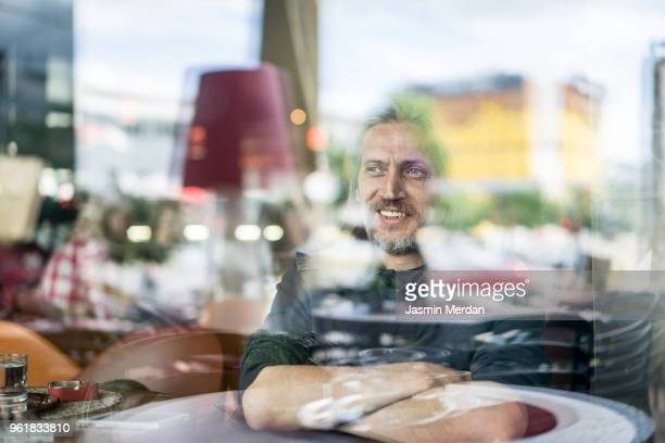 Happy smiling man sitting in coffeeshop