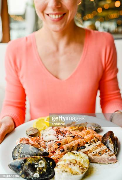 Happy Smiling Mature Woman with plate of grilled seafood