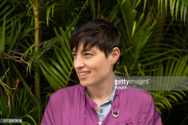 happy smiling person with short hair outside by palm trees miami florida - bomber jacket stock pictures, royalty-free photos & images