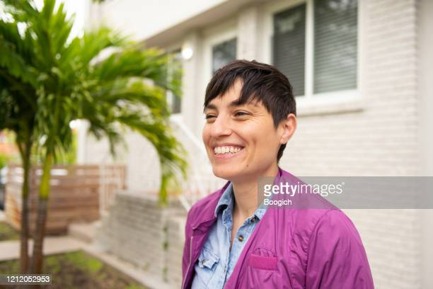 happy smiling person with short hair outside residential building in miami florida - bomber jacket stock pictures, royalty-free photos & images