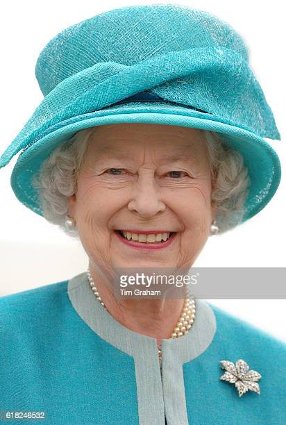 Happy smiling portrait of Queen Elizabeth II in turquoise hat and outfit with diamond brooch and pearls during a visit the Royal Horticultural...