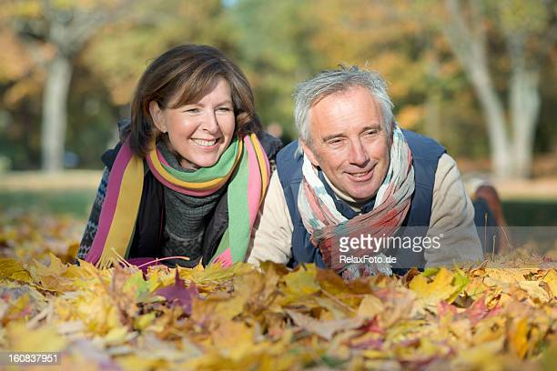 happy smiling senior couple lying on leaves in autumn - alternative lifestyle stock pictures, royalty-free photos & images