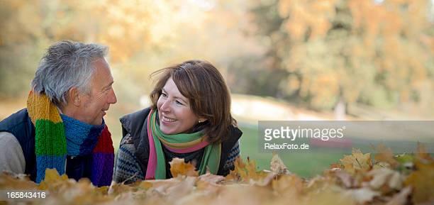 Senior heureux souriant couple allongé sur les feuilles de l'automne