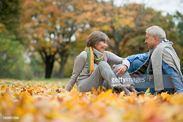 Happy smiling Senior couple sitting on leaves in autumn