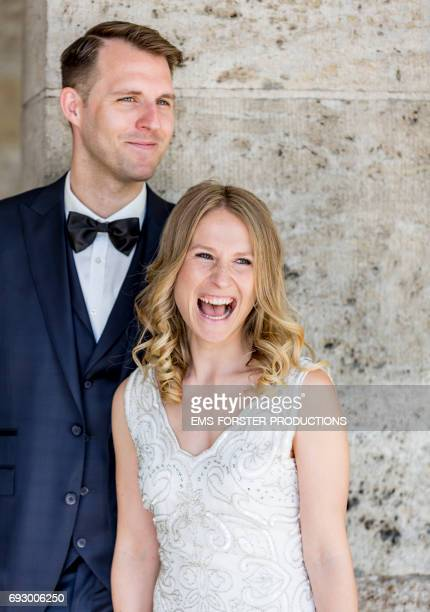 happy smiling tall brown haired groom wearing his wedding suit with fly and his beautiful long blonde haired bride wearing her white wedding dress with a big open smile outdoors in front of the church's wall in bright sunlight right before the wedding
