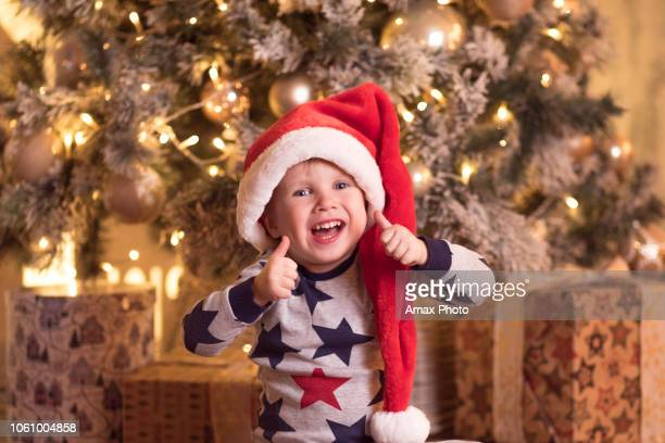 happy smiling toddler boy in a santa hat waiting for new year's eve to open presents. christmas concept with laughing child near christmas tree decorated with garlands and balls - santa face stock pictures, royalty-free photos & images