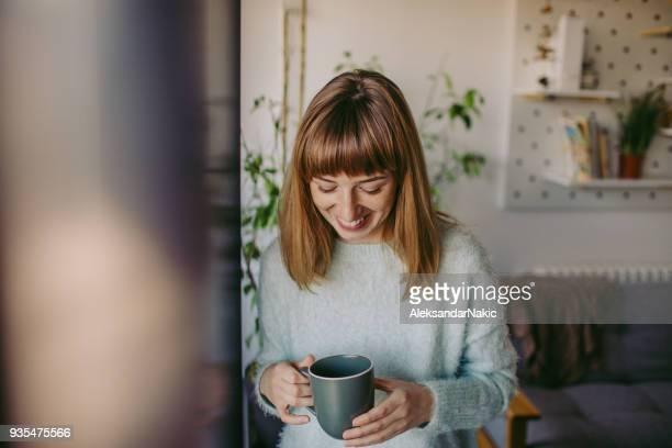 Femme heureuse et souriante, ayant le premier café du matin