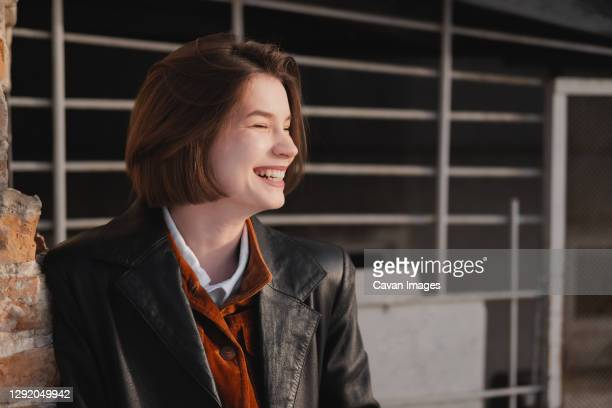 happy smiling woman in leather jacket, direct sunlight and natur - natur stock pictures, royalty-free photos & images